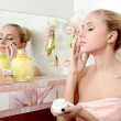 The beautiful woman blonde puts on face a cream — Stock Photo