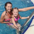 Smiling beautiful woman and her little cute daughter have a fun in pool outdoor — Stock Photo #19990227