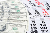 Banknotes of dollars on calendar sheets closeup — Stock Photo