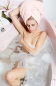 Woman blonde in a bath with foam — Stock Photo