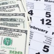 Banknotes of dollars on calendar sheets closeup — Stock Photo