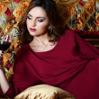 Royalty-Free Stock Photo: Sensual woman with a red wine glass on a magnificent sofa