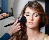 Beautiful girl put the makeup on the face — Stock Photo