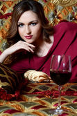 Sensual woman with a red wine glass on a magnificent sofa — Stock Photo