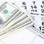 Banknotes of dollars on calendar sheets closeup — Stock Photo #23205104