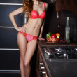 The woman in underwear with a basket of fruit on kitchen — Stock Photo