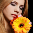 Stock Photo: The beautiful woman with a Gerbera flower on black background
