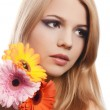 The beautiful woman with a Gerbera flower isolated on white — Stock Photo