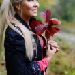 The beautiful young woman with autumn leaves in hands — Stock Photo