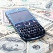 Cellular phone on dollars — Stock Photo