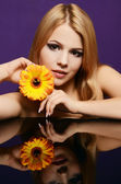 The beautiful woman with Gerbera flower — Stock Photo