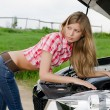 The beautiful girl repairs the car — Stock Photo