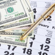 Banknotes of dollars on calendar sheets closeup — Stock Photo #28838909