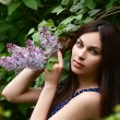 The beautiful woman with flowers of a lilac — Stock Photo