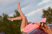 The beautiful girl lays near to red car — Stockfoto