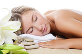 Spa beautiful woman lays with lily — Stok fotoğraf