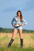 The woman in jeans shorts in the field — Zdjęcie stockowe
