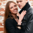 Young enamoured pair a brick wall — Stock Photo