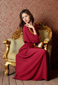 The elegant sensual young woman in a claret dress — Stock Photo