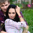 Enamoured young pair in field with flowers — Stock Photo #33424069