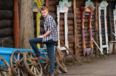 The beautiful man against wooden house — Stock Photo