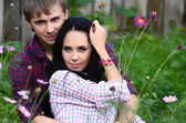 Enamoured young pair in the field with flowers — Stock Photo