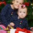 Two little girls at a Christmas fur-tree with gifts — Stock Photo #34350719
