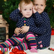 Two little girls at a Christmas fur-tree with gifts — Stock Photo