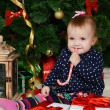 Stock Photo: Little girl at Christmas fur-tree with gifts