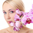 The beautiful young woman with flowers of orchid — Stock Photo