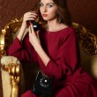 The elegant sensual young woman in a claret dress — 图库照片