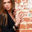 The beautiful woman at an old brick wall — Stock Photo