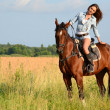 The woman on a horse in the field — Stock Photo #35247105