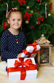 The little girl at a Christmas fur-tree with gifts — 图库照片