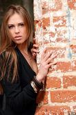 A bela mulher em uma parede de tijolos antigos — Foto Stock