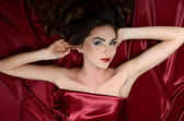 The beautiful woman lays on a red silk fabric — Stock Photo