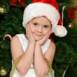 Stock Photo: The little girl at christmas fur-tree