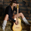 Stock Photo: Womwith guitar on hay