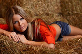 Woman in shorts lays on hay — Stock Photo