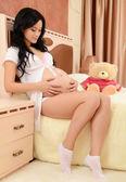 Den gravida kvinnan på en säng i ett rum — Stockfoto