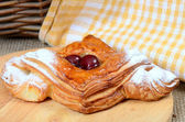 Roll from flaky pastry with cherry — Стоковое фото