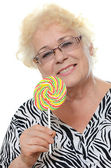 Elderly woman with candy — Stock Photo