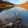 A log and rocks in clear autumn mountain lake with reflection of distant peaks - Stock Photo