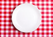 Plate on a tablecloth — Stock Photo