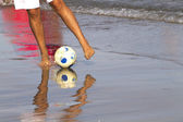 Man on beach balancing soccer ball — Stock Photo