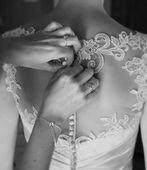 Bridesmaid tying buttons on wedding dress — Stock Photo