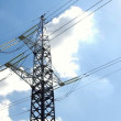 High voltage tower and cables against blue sky - Stock Photo