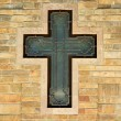 Decorative metal cross on textured wall - Stock Photo