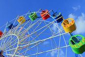 Underside view of a ferris wheel over blue sky — Stock Photo