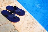 Paar von blau flip flops am rand des schwimmbads — Stockfoto